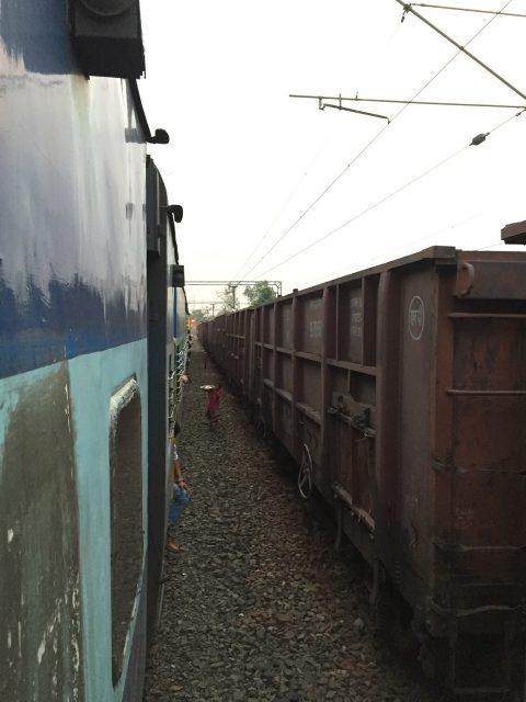 停車中の一コマ。地元の子どもが列車をぬって色々なものを売りに来る。これはココナッツ。ちなみに右の列車は石炭輸送車。